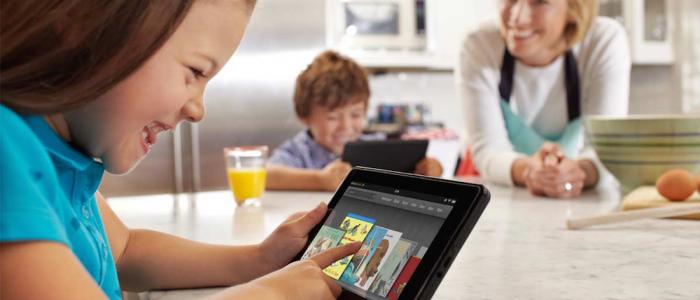 enfant utilisant une tablette en souriant